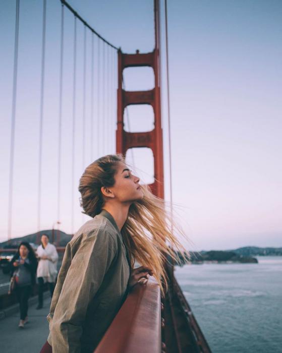 Chica recargada sobre un puente mientras disfruta el aire