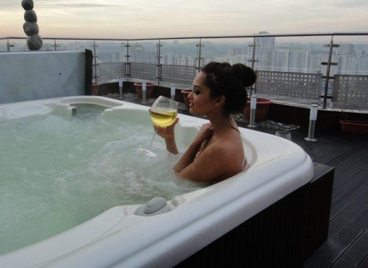 Chica tomando una copa de vino mientras toma un baño al aire libre