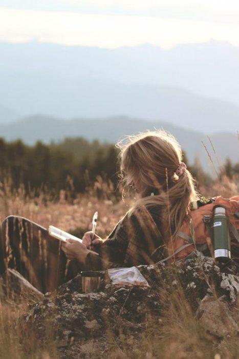 Chica recargada sobre una piedra escribiendo en un libro