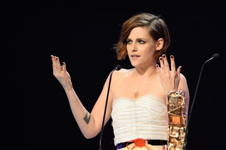 Kristen Stwart con los brazos arriba mientras recibe un premio
