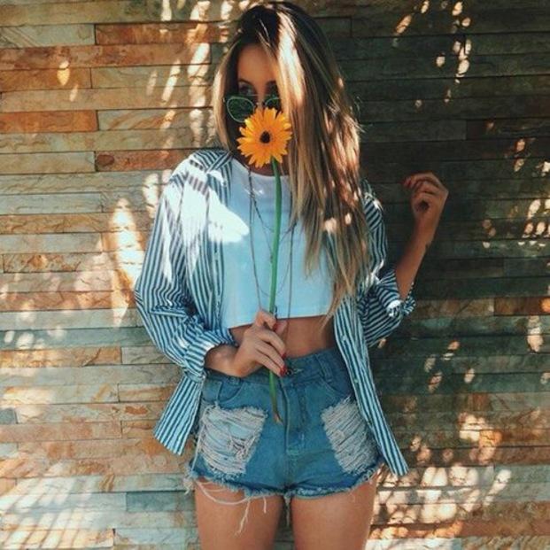 Chica parada sobre una pared oliendo una flor