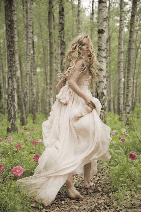 Chica corriendo por un campo de flores