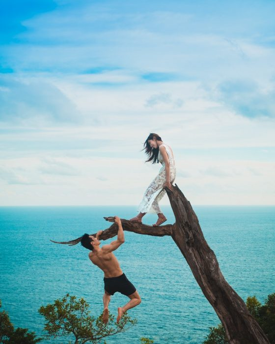 pareja en un tronco frente al mar