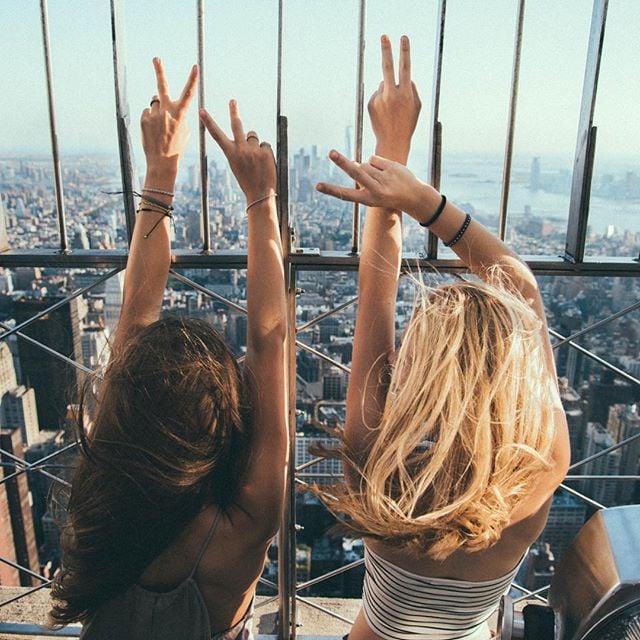 dos mujeres de espaldas viendo a la ciudad en la ventana