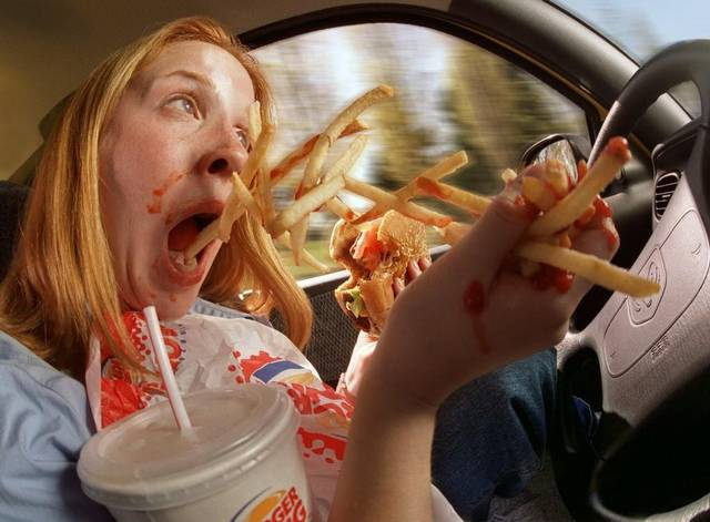 mujer comiendo mientras maneja