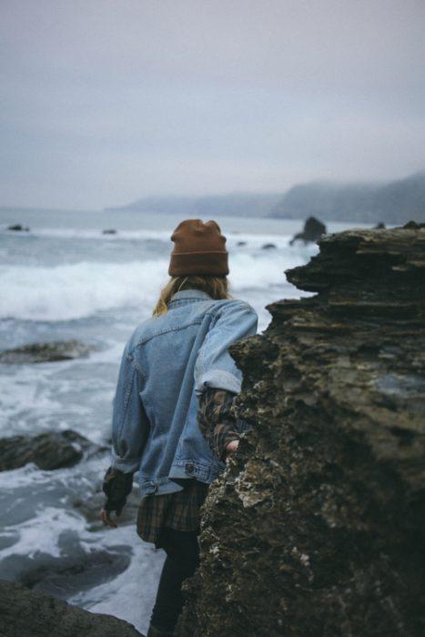 chica caminando entre rocas en la playa