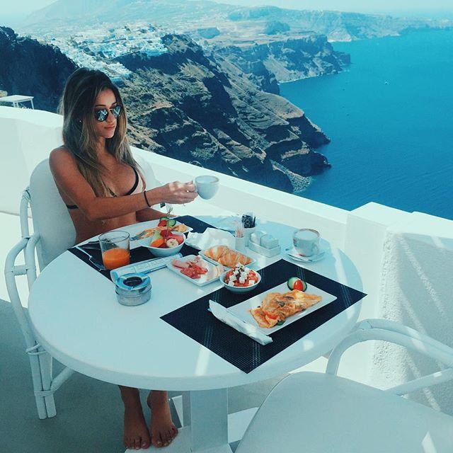 Chica sentada frente a una piscina comiendo
