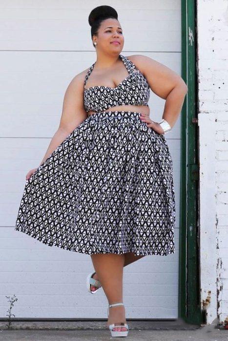 Chica curvi usando un crop top con falda en un diseño de estampados de bolitas