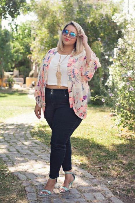 Chica curvi usando un crop top en color blanco con un pantalón de mezclilla