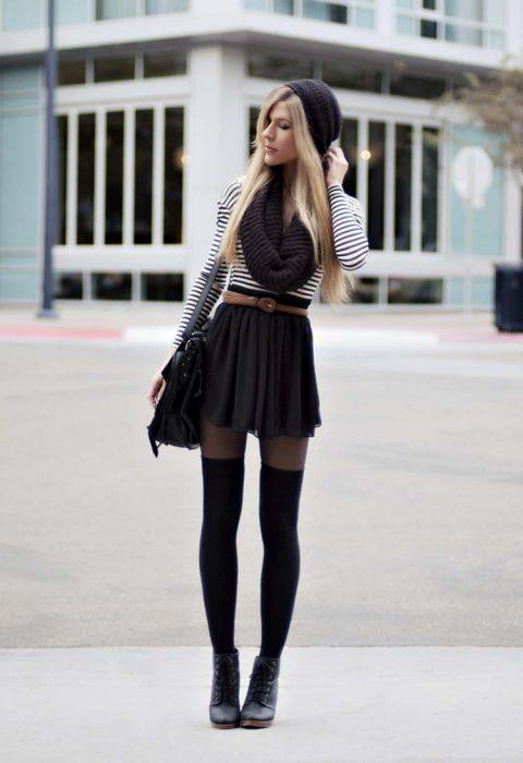 mujer con falda corta y medas largas gorro y bufanda