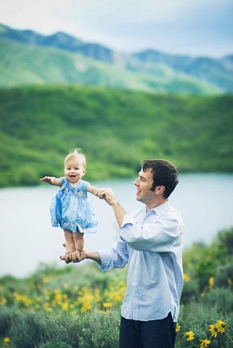Padre sujetando a su hija de las piernas