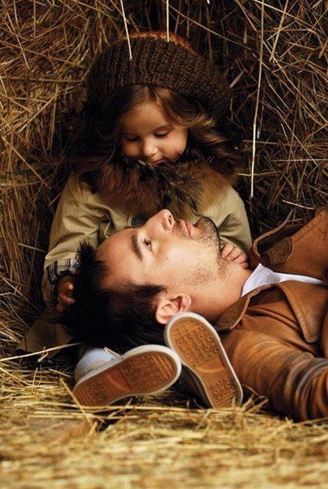 Padre e hija sentados en un establo viéndose fijamente