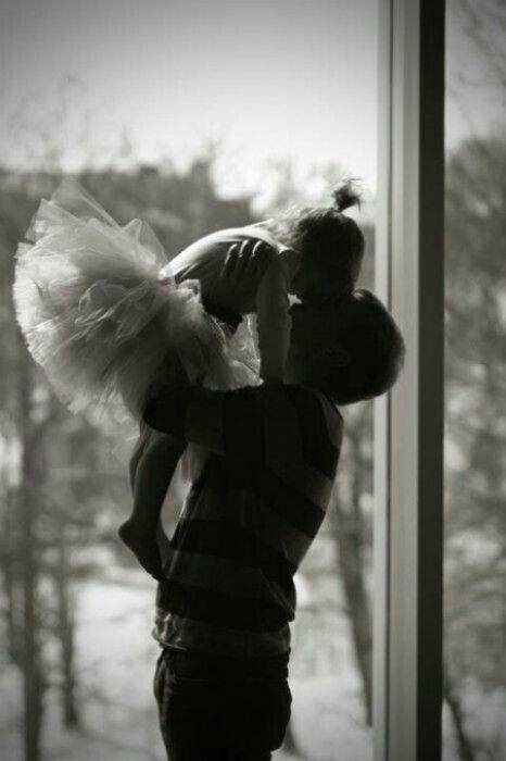 Padre sosteniendo a su hija que está usando un tutu