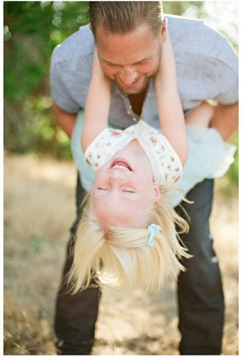 Padre jugando con su hija mientras ella ríe