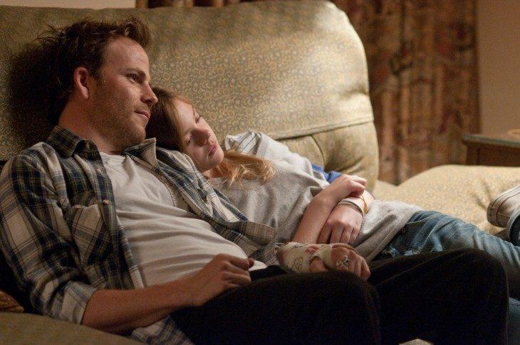 Padre e hija recostados en la cama conversando