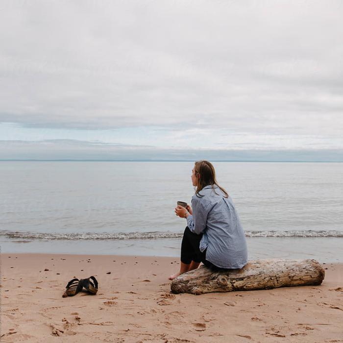chica rubia sentada en la playa con una taza de café