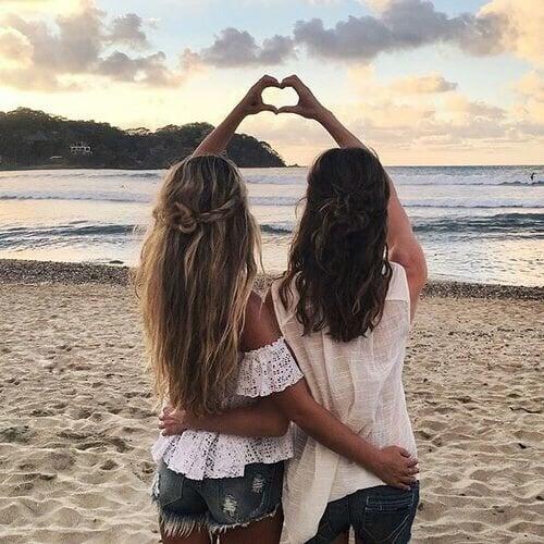 chicas en la playa haciendo señal con manos