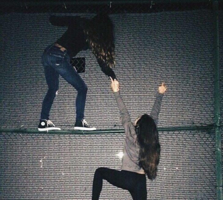 chicas intentando subir una barda