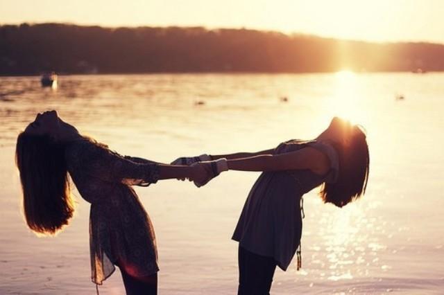 chicas tomadas de la mano en al playa