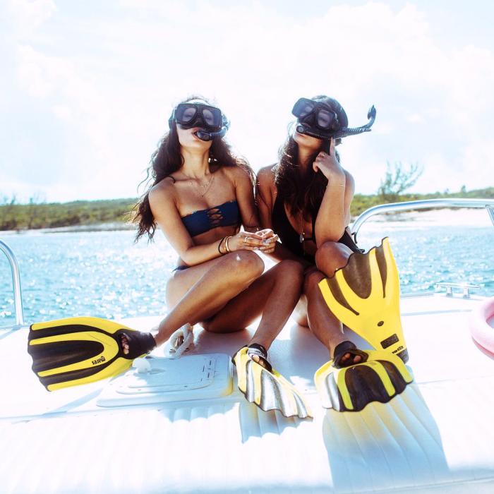 Chicas sentada en un bote usando equipo para bucear