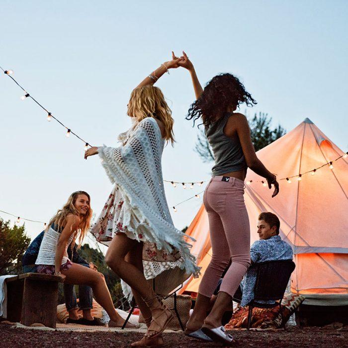 Chicas bailando frente a una fogata