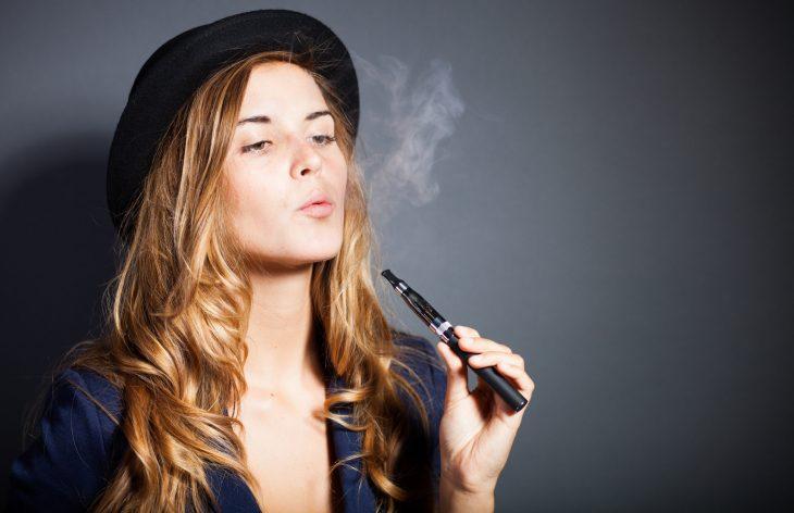 Chica fumando un cigarrillo electrónico
