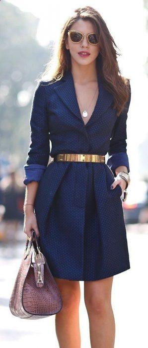 Chica usando un vestido azul con un cinturón dorado