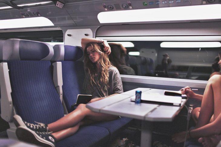 mujer sentada en asiento de tren leyendo libro con brazo en la mano