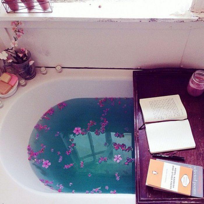 tina de baño con flores y una tabla con libros