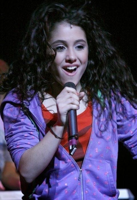 chica adolescente de cabello negro cantando con microfono