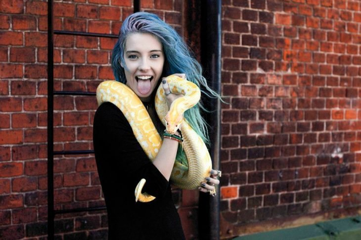 Chica sosteniendo una víbora amarilla en su cuello