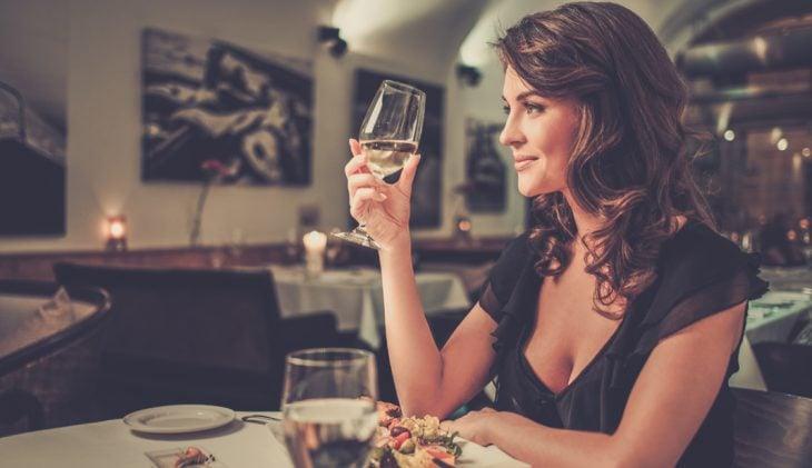 Chica sosteniendo una copa de vino mientras cena sola