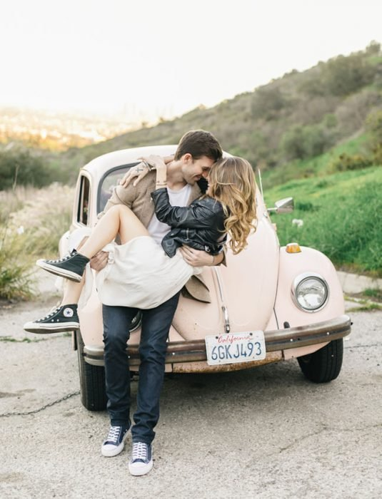 Pareja de novios besándose frente a un carro