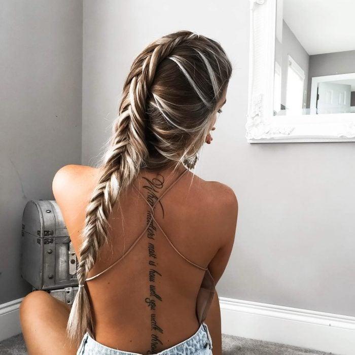 Chica sentada en la cama mostrando su tatuaje