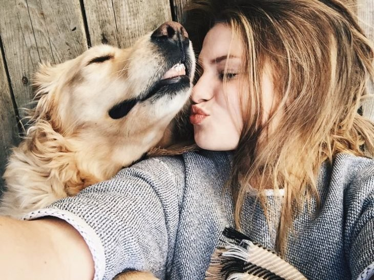 chica linda con un perro le da un beso