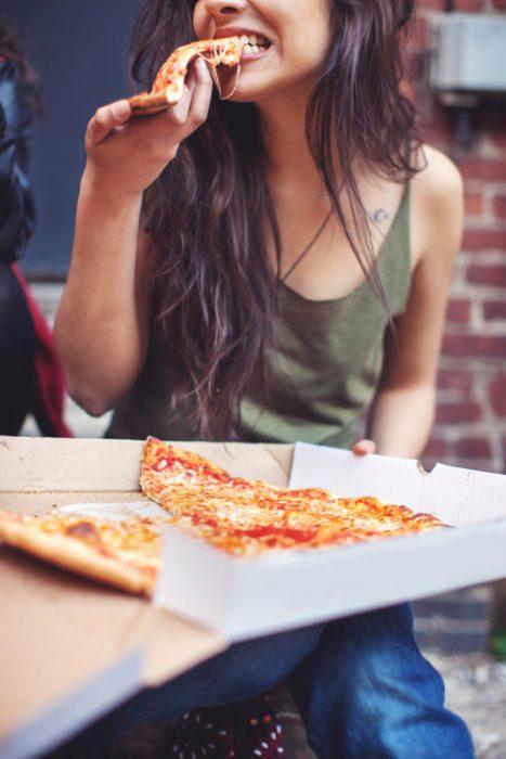 chica comiendo pizza