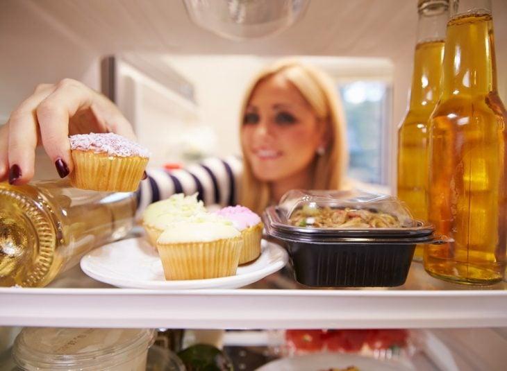 chica comiendo pastelillo del refrigerador