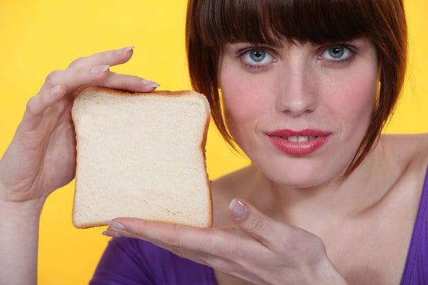 chica mostrando una rebanada de pan