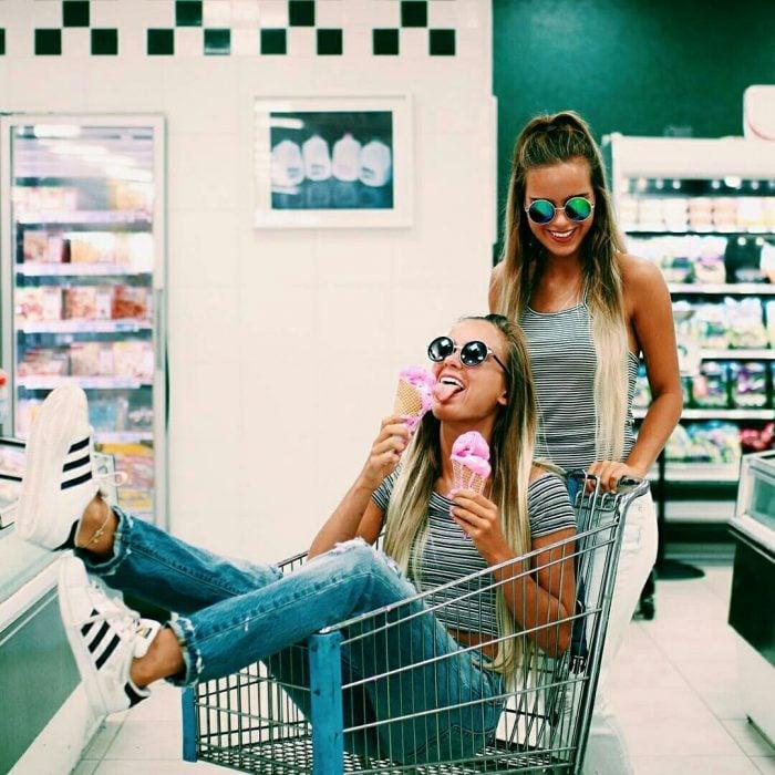 Amigas paseando en un carro de supermercado