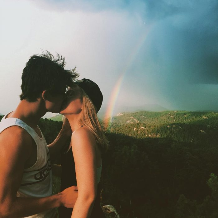 pareja besándose con arcoíris de fondo