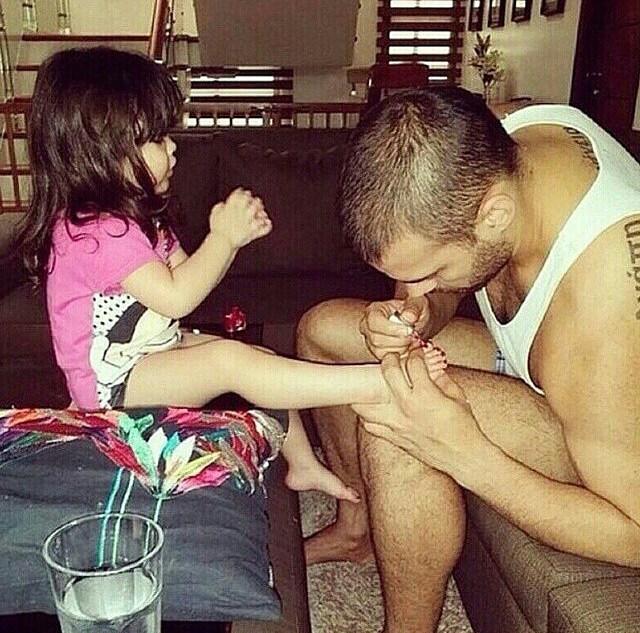 padre pintando uñas de los pies a niña