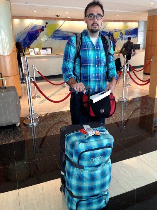 hombre vestido igual que maleta