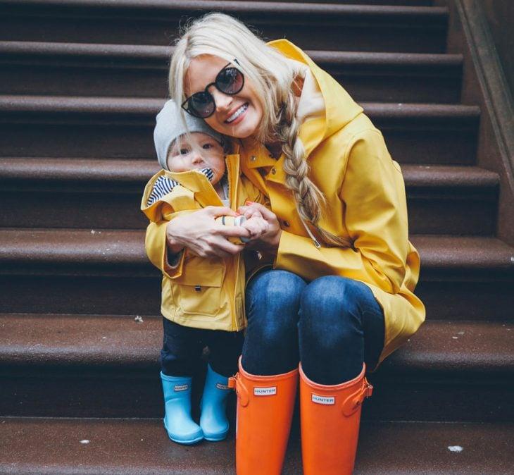 mujer rubia abrazando a su hijo con botas de lluvia