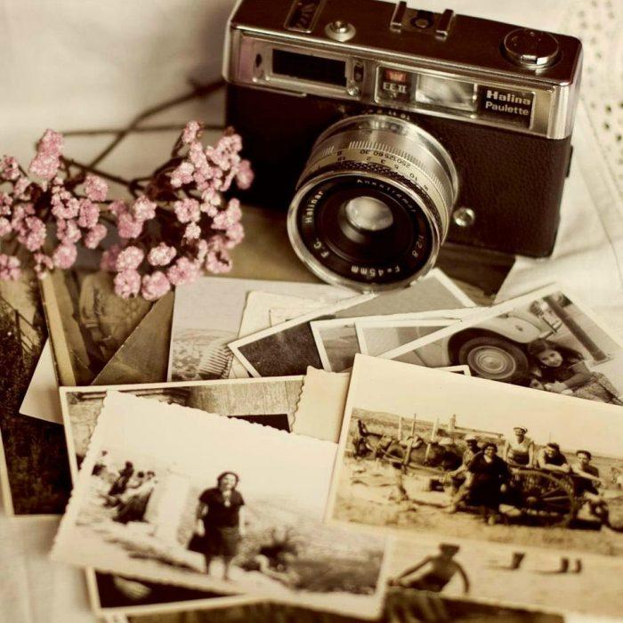 cámara fotográfica con fotografías antiguas y flores