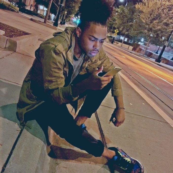 hombre moreno sentado en la calle con un celular
