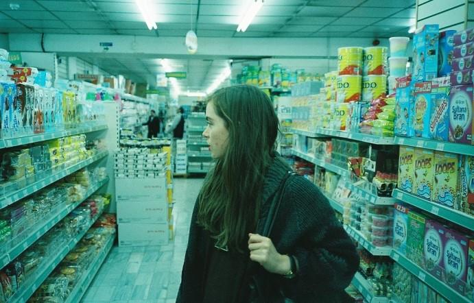 chica en super mercado sola con una mochila