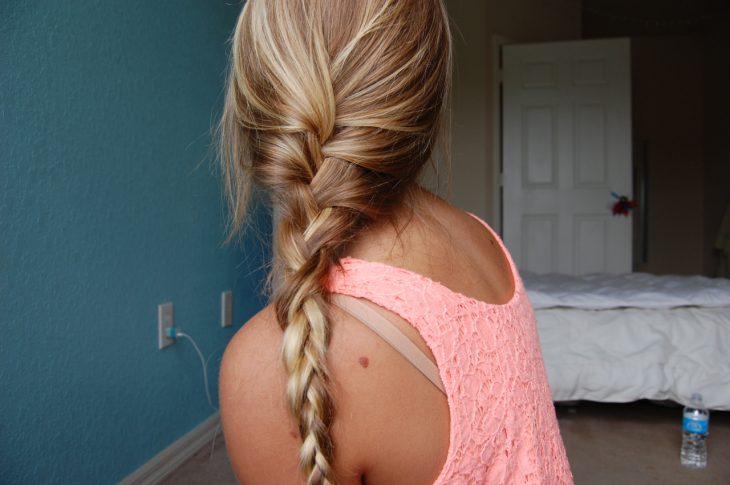 Chica sentada en su cama con el cabello trenzado