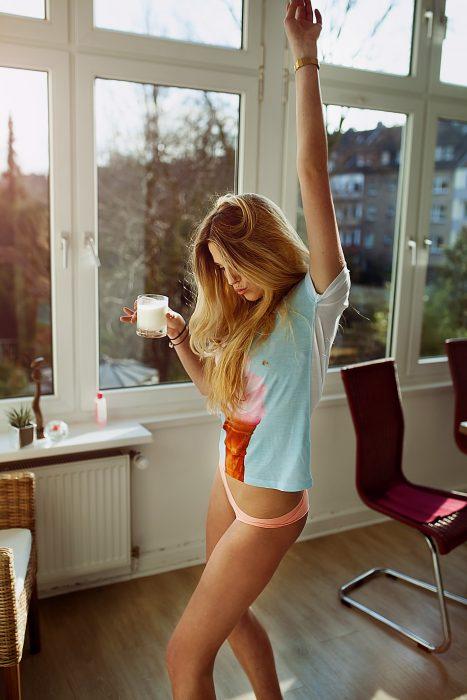 Chica sosteniendo un vaso de leche mientras baila en medio de la sala