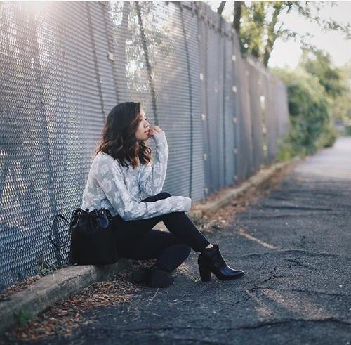 Chica sentada en medio de una acera mordiendo sus uñas