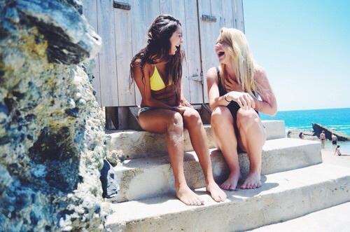 Chicas sentadas sobre escalones mientras ríen y ven el mar